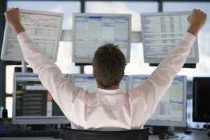 Rear view of stock trader with hands raised looking at multiple